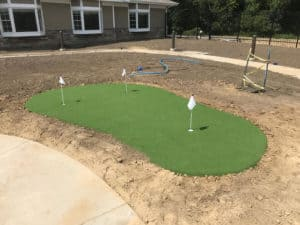 A putting green using artificial grass in the later stages of a landscape design project.