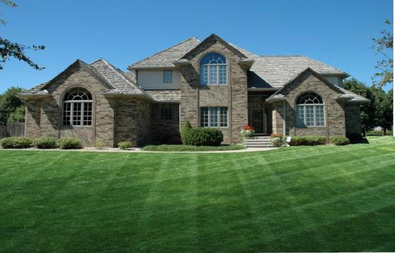 A beautiful yard in front of a home with clean lines created by Heroes grass cutting service.