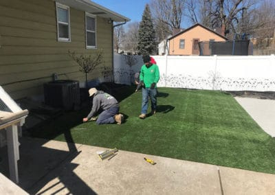 Heroes' lawn care experts installing turf next to a beautiful hardscape walkway.