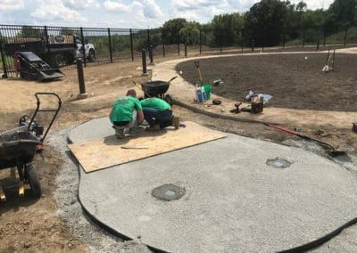 Two landscaping contractors in the early stages of building a putting green during a lawn installation job.