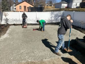 Professional lawn care experts preparing the ground for new landscape installation.