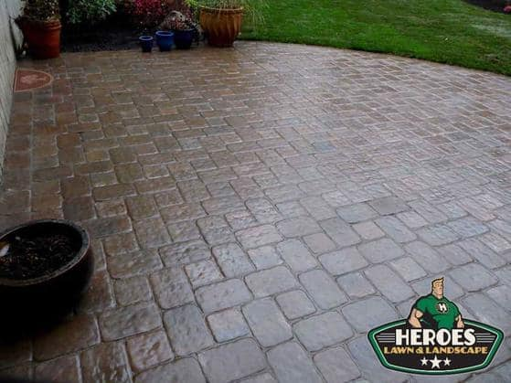 A patio hardscape design with lush green grass in the background.