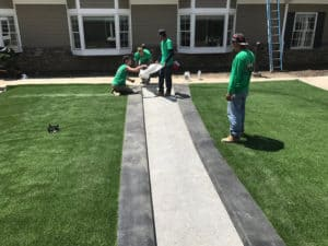 Heroes' landscapers paying close attention to detail while installing a new lawn using artificial turf.