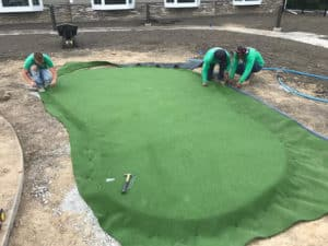 Heroes' landscaping experts using artificial turf during a lawn installation.